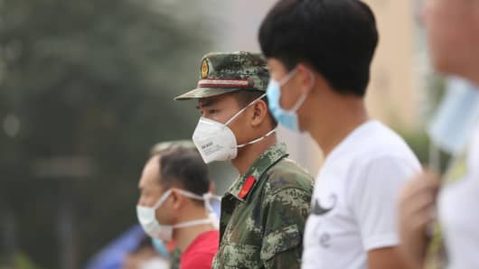 Volunteers and paramilitary soldiers wearing masks stand on patrol outside a temporary shelter after the explosions in Tianjin on August 14, 2015.