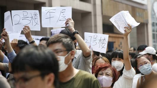 Residents, whose homes were destroyed in the explosion at a chemical warehouse last week, protest outside the hotel where authorities were set to hold a press conference in Tianjin.