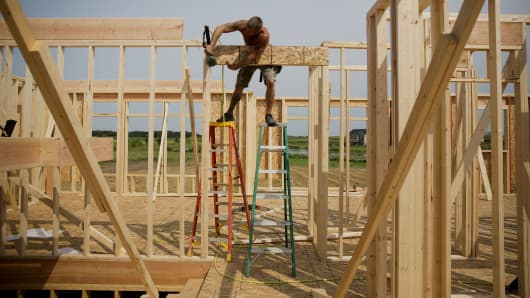 A contractor installs a door header inside a house under construction for Ironwood Homes in Peoria, Illinois.