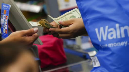 A customer receives cash change from a cashier at a Walmart in the Porter Ranch neighborhood of Los Angeles.