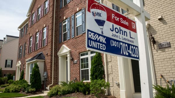 A 'For Sale' sign sits in the front yard of a townhouse in Northeast Washington, DC.