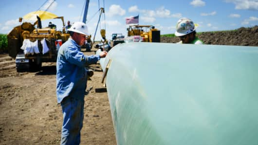 Workers work on an oil line pipeline in Decatur, IL.