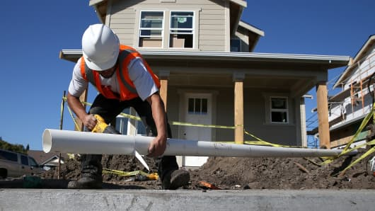 A worker cuts a piece of pipe as he builds a new home in Petaluma, California.