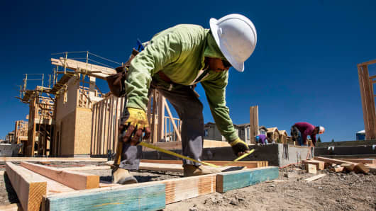 A worker measures wood for a house under construction at the KB Home Vineyard Crossing Community in Livermore, California.