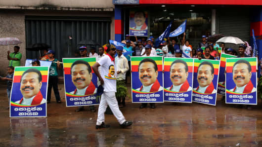 COLOMBO, SRI LANKA - AUGUST 17: Supporters hold posters of the former Sri Lankan president and parliamentary candidate Mahinda Rajapakse in the rain at the end of voting in the General election on August 17, 2015 in Colombo, Sri Lanka.
