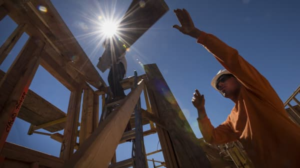 Workers load wood planks on a house under construction at the KB Home Vineyard Crossing Community in Livermore, California.
