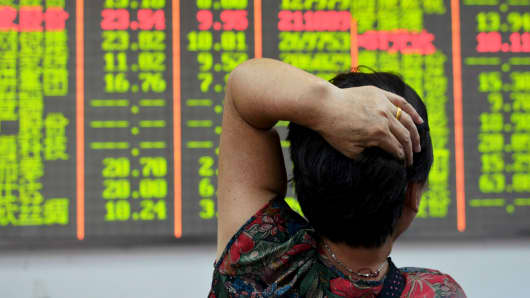 An investor looks at an electronic board showing stock information in Hangzhou, China.