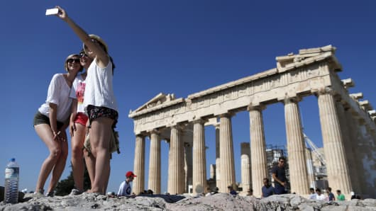 A group of tourists take a selfie in front of the temple of the Parthenon atop the Acropolis in Athens, Greece.