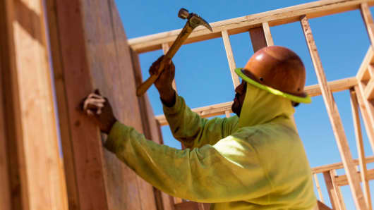 A worker nails siding on a house under construction in Livermore, California.