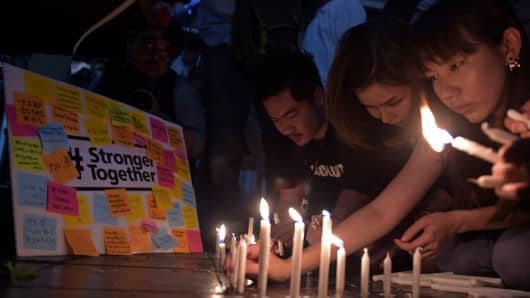 Candles are lit for victims killed in a bomb blast outside Erawan shrine in Bangkok.
