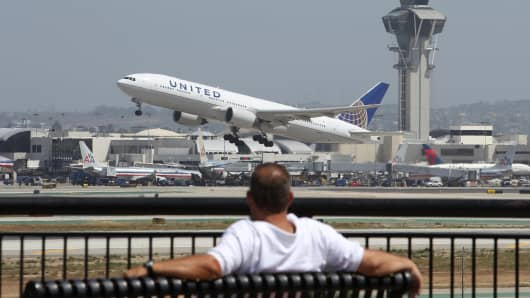 A United Airlines jet passes the air traffic control tower at Los Angles International Airport (LAX) during take-off in Los Angeles, California.