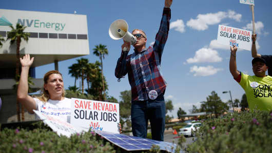 Max Britton, center, speaks during a rally in front of NV Energy, Wednesday, April 22, 2015, in Las Vegas.