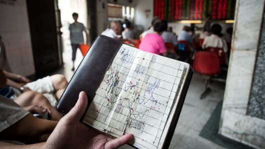 An investor holds a notebook showing stock market movements, as he sits at a brokerage house in Shanghai, China.