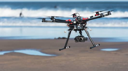 An octocopter photographic drone, equipped with a video camera, hovers over a beach.