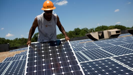 Employees of SunEdison install photovoltaic solar panels in Hillsborough, New Jersey.