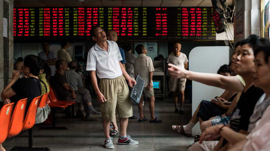 Investors monitor screens showing stock market movements at a brokerage house in Shanghai
