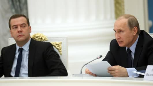 Russian President Vladimir Putin (R) and Prime Minister Dmitry Medvedev (L) attend a meeting in Moscow in May 2015.