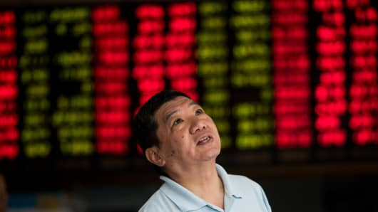 An investor monitors screens showing stock market movements at a brokerage house in Shanghai, China.