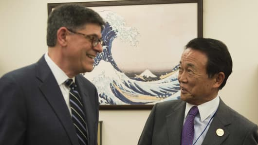 Japanese Finance Minister Taro Aso (R) talks with US Treasury Secretary Jacob Lew before a bilateral meeting during the IMF/World Bank Springh Meetings in Washington, DC, April 16, 2015.