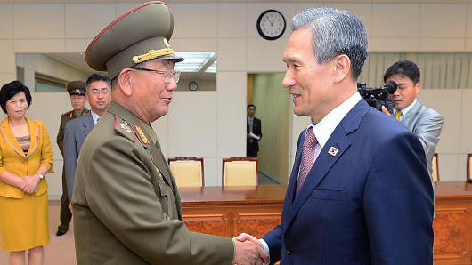 South Korean presidential security adviser Kim Kwan-Jin (R) shakes hands with Hwang Pyong-So (L) North Korea' top political officer for the Korean People's Army after their meeting at the Panmunjom on August 25, 2015 in Paju, South Korea. Both countries came to an agreement to ease tensions after an exchange of artillery fire last week.
