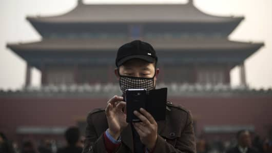 A Chinese man uses his smartphone on a hazy day outside the Forbidden City in Beijing, China.