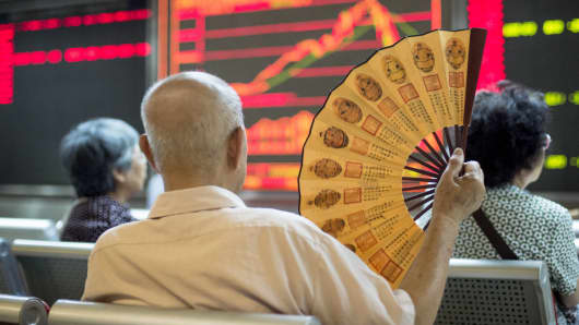 Investors look at screens showing stock market prices at a securities company in Beijing.