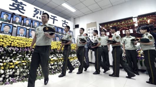 August 18, 2015: Paramilitary police mourn for firefighters and soldiers killed during the explosions in Tianjin. With a swathe of one of the world's busiest ports in ruins, more than a billion dollars in losses, and some major multinational firms still unable to access their premises, the economic impact of the Tianjin explosions could reverberate for months.