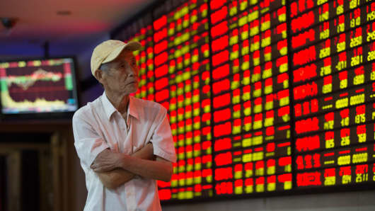 An investor watches the stock market at a stock exchange hall in Shanghai, China.