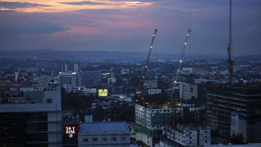 Cranes operate on a residential building under construction at dusk in Cebu, Philippines.