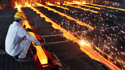 A worker cuts steel billets at an iron and steel enterprise in Ganyu County.