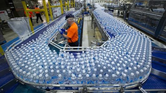 A worker inspects bottles of water at a Nestle Waters plant.