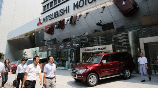 Pedestrians walk past the headquarters of Japanese automaker Mitsubishi Motors in Tokyo, Japan.