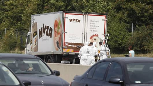 Forensic officers stand in front of a truck inside which were found a large number of dead migrants on a motorway near Neusiedl am See, Austria, on August 27, 2015.