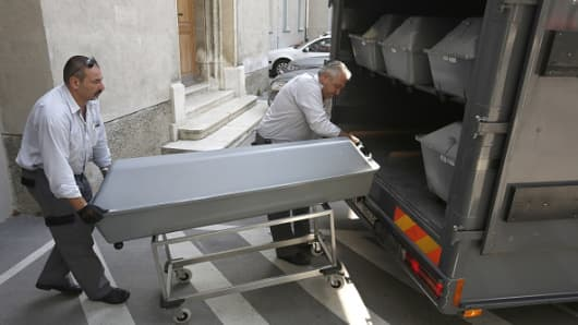 First 10 coffins with bodies of migrants who died in an abandoned lorry are unloaded from a van on August 28, 2015 for an investigation at a forensics institute in Vienna.