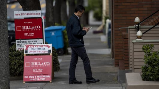 A real estate checks his mobile phone while waiting for potential home buyers in the Castro district of San Francisco.