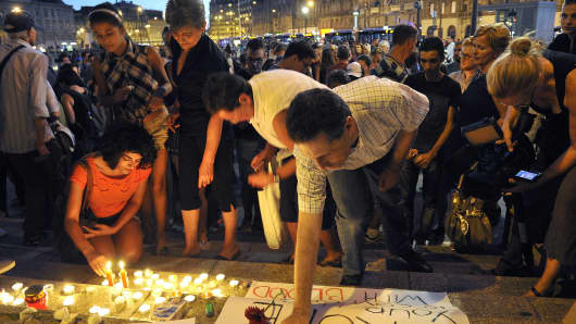 People light candles next to banner reading 'Europe,your hand is covered with blood' in front of the Eastern railway station and nearby the transit zone of migrants in Budapest on August 28, 2015 to commemorate more than 70 dead migrant victims found in a truck in Austria.