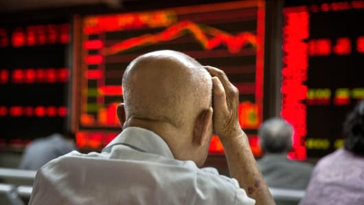 A man watches stock prices at a brokerage in Beijing, China.