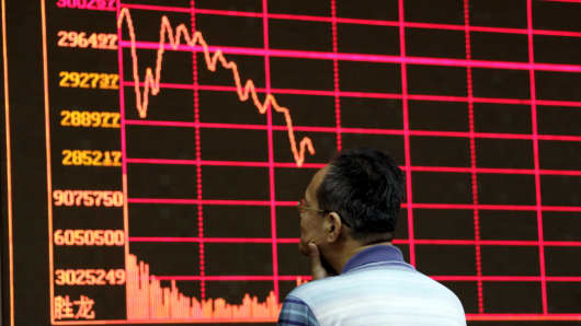 An investor examines the Shanghai Stock Exchange Composite Index at a brokerage house in Beijing, August 26, 2015.
