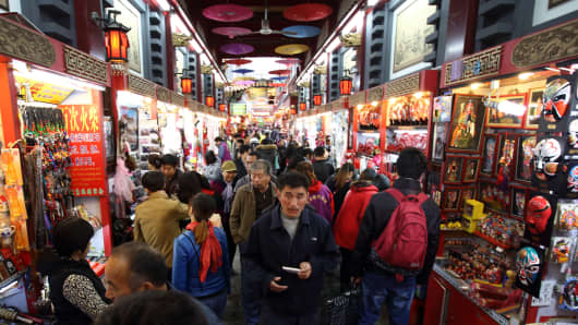 Shoppers peruse vendors' wares on a street in Beijing
