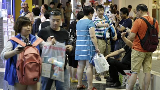 A group of Chinese tourists stand with shopping bags at the Canal City Hakata commercial complex in Fukuoka, Japan, on Friday, July 24, 2015. Four million Chinese tourists are expected to head to Japan this year.