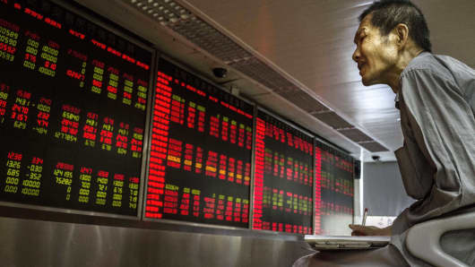 A Chinese day trader takes notes on the activity of the market he watches a stock ticker at a local brokerage house in Beijing, China.