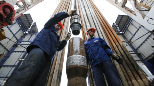 Workers secure drilling pipe sections on an oil drilling tower