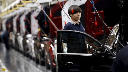 An employee works on an assembly line producing Mercedes-Benz cars in Beijing, August 31, 2015.
