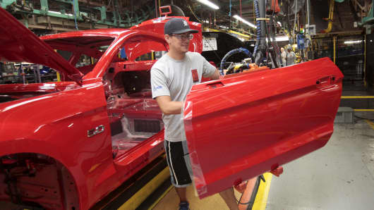 A Ford Motor assembly worker works on a Ford Mustang at the Ford Motor Flat Rock Assembly Plant in Flat Rock, Michigan.
