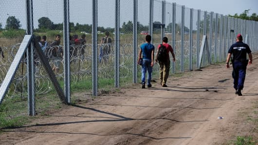 Migrant people walk on both sides of the metal fence near the Hungarian village of Asotthalom of the Hungarian-Serbian border.