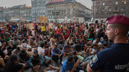 Hungarian police guard the main entrance as migrants protest outside Keleti station in central Budapest after it was closed to migrants on September 1, 2015.