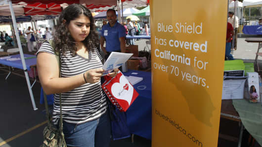 A woman gets information from the Blue Shield of California booth at the East Los Angeles Health Fair held at Griffith Middle School on September 21, 2013 in East Los Angeles.