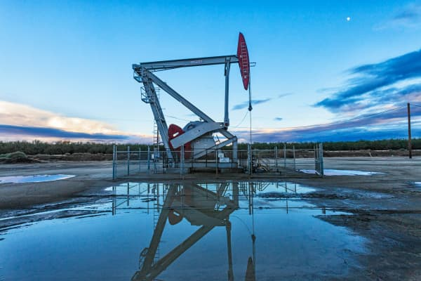 A pump jack and surface water at oil well and fracking site in Shafter.