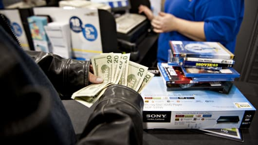 A customer counts his money as he prepares to pay for merchandise at a Best Buy store in Peoria, Ill.