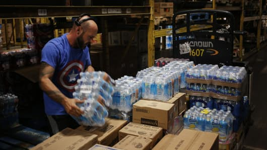 A worker stacks cases of bottled water for delivery to stores at the Associated Wholesale Grocers distribution warehouse in Goodlettsville, Tennessee, U.S., on Friday, Aug. 14, 2015.